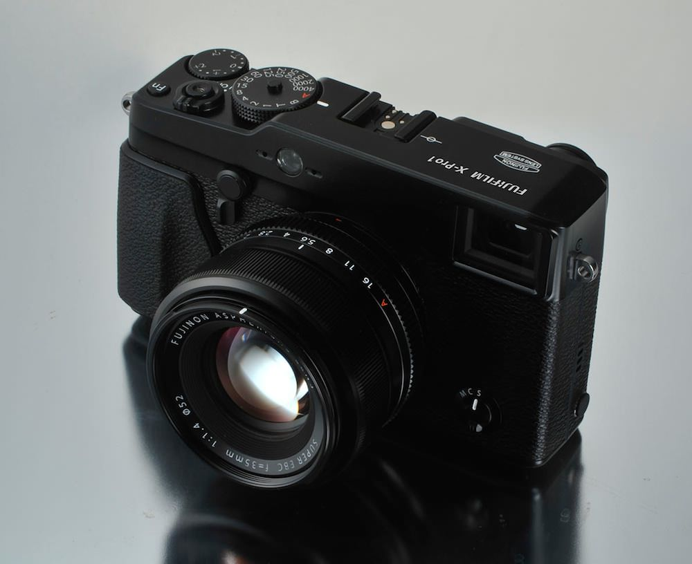 ... Fujifilm X-Pro1 camera with 35mm lens on surface ...